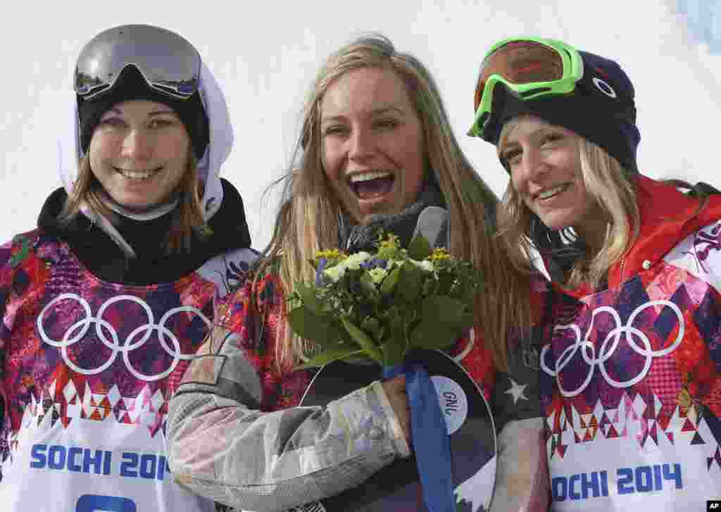 Jamie Anderson of the United States, center, celebrates with silver medalist Enni Rukajarvi of Finland, left, and bronze medalist Jenny Jones of Britain, after Anderson won gold in the women's snowboard slopestyle, Krasnaya Polyana, Russia, Feb. 9, 2014.