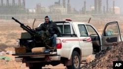 FILE - An anti-government rebel sits with an anti-aircraft weapon in front an oil refinery in Ras Lanouf, eastern Libya, March 5, 2011. The United States, France, Germany, Italy, Spain and Britain have called upon forces loyal to a Libyan general to withdraw from three eastern oil terminals seized earlier this week, in a statement, Sept. 13, 2016.