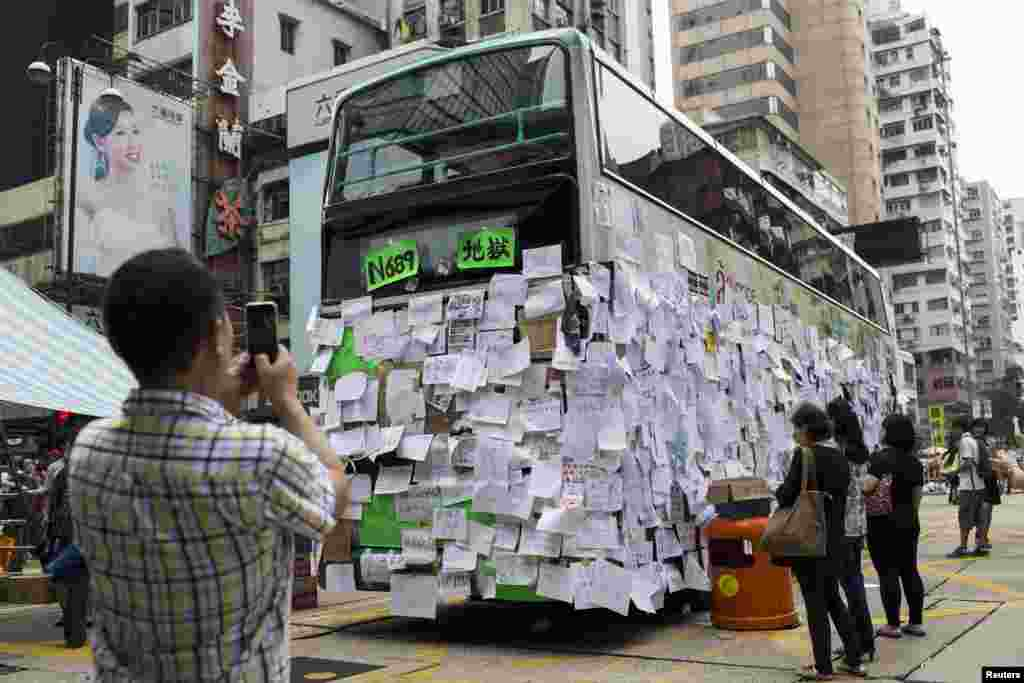 A man takes a picture of a bus covered with messages of support at Mongkok shopping district after thousands of protesters blocked the road in Hong Kong, Sept. 30, 2014.