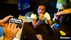 Una niña usa una máquina Braille para ecribir en su iPhone en Nueva York.