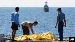 인도네시아 수색요원들이 23일 자바 해저에서 인양한 에어아시아기 탑승사 시신을 수습하고 있는 모습.