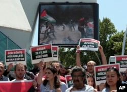 "Turkish protesters hold placards that read "" Free Palestine"" and "" Struggle to return back home continue for 70 years "" as they stage a protest near the U.S. embassy in Ankara, Turkey, May 15, 2018."
