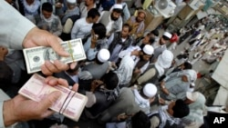 An Afghan trader holds U.S. dollar and Afghani bundles at the Saray- e Shahzadeh, the main exchange market in Kabul, Afghanistan, Sept. 18, 2011.