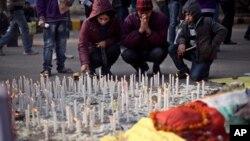 Satu keluarga India menyalakan lilin untuk mengenang perempuan korban perkosaan beramai-ramai di New Delhi bulan lalu, hari Sabtu (5/1).