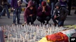 一個印度家庭星期六在新德里點燃蠟燭哀悼一名輪姦受害者