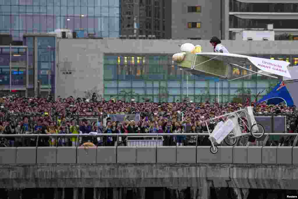 """A participant operates the """"Flying Dim Sum"""", a self-made flying machine, during the Red Bull Flugtag (Flight Day) event at Hong Kong's financial Central district."""