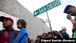 Di dân từ Trung Mỹ xếp hàng nhận quà sáng tại một trại tị nạn ở Tijuana, Mexico.