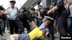 "Policemen break up a fight between a gay rights activist and an anti-gay rights activist (in yellow) during a protest against a proposed new law termed by the lower house of Parliament, as ""against advocating the rejection of traditional family values"" in central Moscow June 11, 2013."