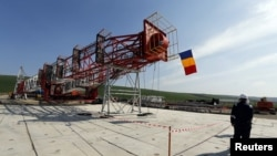 FILE - A worker walks in front of the drilling tower at Chevron's site during a media day in Pungesti.