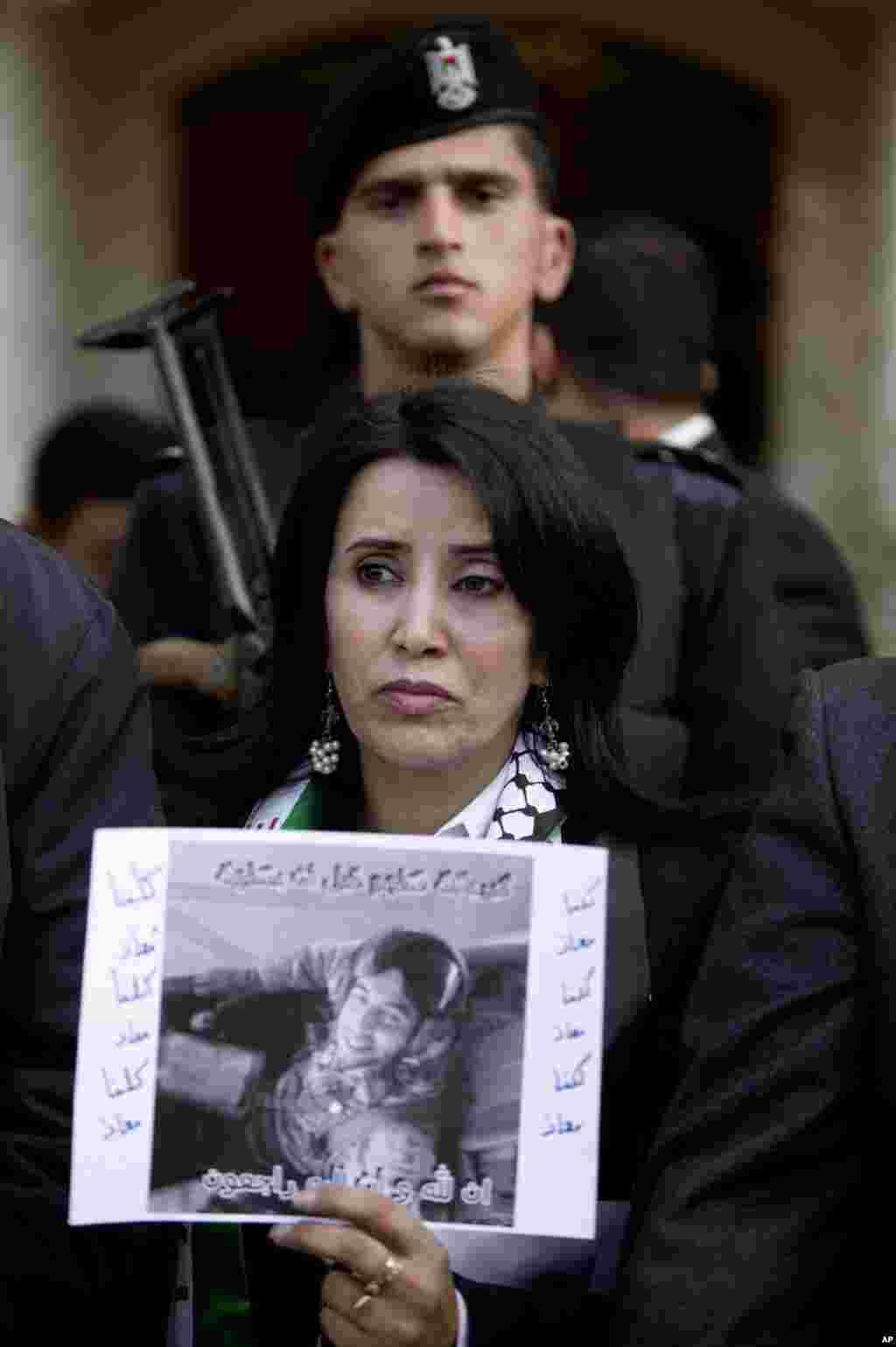 زن فلسطینی در جریان اعتراض در مقابل سفارت اردن، در رام الله در کرانه غربی پوستری با عکس ستوان معاذالکساسبه، خلبان مقتول اردنی، بدست دارد -- ۱۵ بهمن ۱۳۹۳ (۴ فوريه ۲۰۱۵)