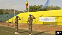Peacekeepers of the United Nations Multidimensional Integrated Stabilization Mission in Mali (MINUSMA) salute Mali and UN flags on May 29, 2015, in Bamako.