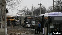 Buses wait along a road while travelling in the direction of the village of Debaltseve, Feb. 6, 2015.