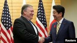 Menteri Luar Negeri Amerika Mike Pompeo (kiri) berjabat tangan dengan PM Jepang Shinzo Abe, di Tokyo, Jepang, 6 Oktober 2018.