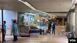 多名穿上保護衣的警員封鎖連接康美樓及街市的一個出入口。(美國之音 湯惠芸拍攝)
