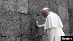Đức Giáo hoàng Phanxicô cúi đầu cầu nguyện tại Bức tường Chết chóc của trại tập trung Auschwitz-Birkenau, Ba Lan, ngày 29/7/2016.
