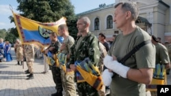 FILE - Volunteers of battalion 'Donbas' hold battalion flags during a blessing ceremony in St. Michael Cathedral in Kyiv, Ukraine.