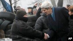 克里(右)在基輔與一名烏克蘭示威者握手