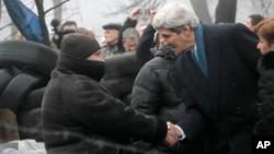 Ngoại trưởng Mỹ John Kerry bắt tay với một người biểu tình bên cạnh những chướng ngại vật tại thủ đô Kyiv của Ukraina, ngày 4/3/2014.