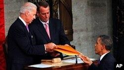 Avant de prononcer son discours dans l'enceinte du Capitole, le président Obama (à dr.) en remet le texte, comme le veut la tradition, au vice-président Joseph Biden (à g.), à titre de président du Sénat, et au républicain John Boehner, président de la Ch
