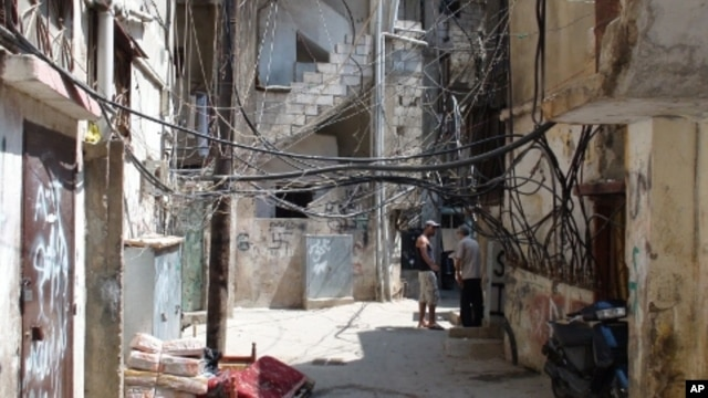 A tangle of electrical wires and water pipes, and anti-Semitic graffiti line the alleyways of the Shatila refugee camp in Lebanon, 31 Aug 2010