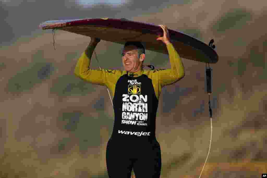 Garrett McNamara ôm tấm ván trợt sau chuyến lướt sóng phá kỷ lục ở Bồ Đào Nha.