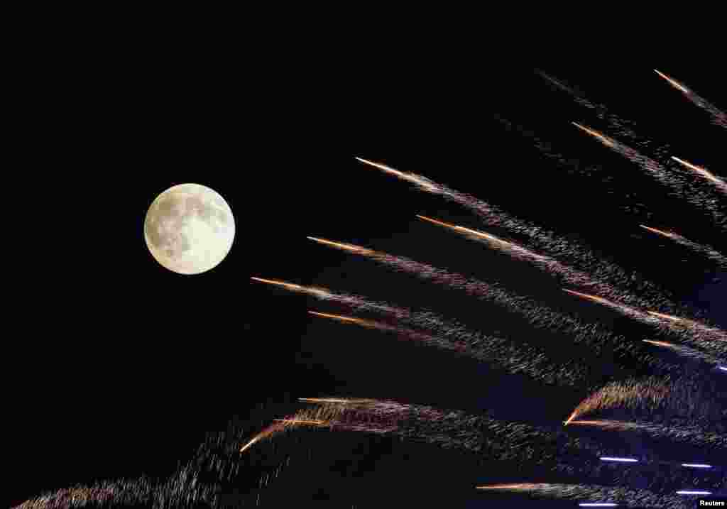 Fireworks streak past in front of the supermoon outside the town of Mosta, celebrating the feast of its patron saint, in central Malta, Aug. 10, 2014.