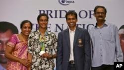 P.V. Sindhu, deuxième à gauche, qui a remporté une des deux médailles de l'Inde aux Jeux Olympiques de Rio de Janeiro pose avec son entraîneur Pullela Gopichand, deuxième à droite, la mère, P. Vijaya, à gauche, et le père, P.V. Ramana, à droite, au cours de leur réception au Gopichand Acade., Inde