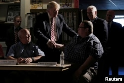 Republican nominee Donald Trump and his running mate Indiana Governor Mike Pence (back R) meet with local labor leaders and union members during a campaign stop in Brook Park, Ohio, Sept. 5, 2016.