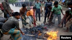 ປະຊາຊົນໃນທ້ອງຖິ່ນ ພາກັນດັບໄຟ ໃນຂະນະທີ່ ພວກຕໍາຫລວດກໍາລັງທຳການລາດຕະເວນ ລຸນຫລັງທີ່ພວກນັກເຄື່ອນໄຫວ Jamaat-e-Islami ຈູດໄຟໃສ່ຮ້ານຂາຍຝ້າຍ ຢູ່ໃກ້ ສະຖານີລົດໄຟ Kamalapur ຢູ່ນະຄອນ Dhaka ໃນວັນທີ 1 ສິງຫາ 2013.