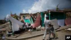 A man carries a presidential election poster past a destroyed kindergarten in Les Anglais, Haiti, Oct. 10, 2016. Presidential elections scheduled for the previous day were postponed after the passage of Hurricane Matthew.