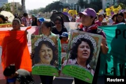 Activists hold pictures of slain environmental rights activist Berta Caceres during a protest to mark International Women's Day outside the presidential house in Tegucigalpa, Honduras, March 8, 2016.