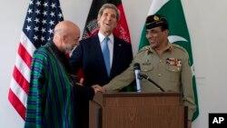 Menlu AS John Kerry (tengah) tertawa sementara President Afghanistan Hamid Karzai (kiri) dan Pemimpin militer Pakistan Jenderal Asfhaq Parvez Kayani berjabat tangan setelah pertemuan di Brussels, Belgia (24/4).