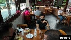 Posetioci sede za stolovima uređenim tako da se poštuju mere društvenog distanciranja između gostiju, u restoranu, dok grad olakšava restrikcije uvedene zbog epidemije koronavirusa, u Sao Paulu, Brazil 6. jula 2020. (Foto: Rojters/Amanda Perobelli)