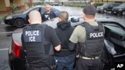 FILE - This photo released by U.S. Immigration and Customs Enforcement shows foreign nationals being arrested during a targeted enforcement operation aimed at immigration fugitives, re-entrants and at-large criminal aliens in Los Angeles, Feb. 7, 2017.