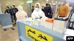 Des agents de la santé se préparent à prendre la température corporelle des voyageurs qui arrivent à l'aéroport international du Caire le 1er février 2020, (AFP)