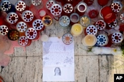 "FILE - Candles, notes and paper cuttings lie next to the ""Love Monument"" in St. Julian, Malta, Oct. 17, 2017, the day after the killing of journalist Daphne Caruana Galizia."