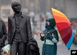 FILE - A youth wearing a face mask looks up at statue of John Lennon, part of a larger statue of The Beatles in Liverpool, England, Monday Oct. 12, 2020, as Prime Minister Boris Johnson prepares to lay out a new three-tier alert system for England.