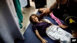 24일 가자지구 유엔 학교 시설에 이스라엘 군의 공습이 있은후, 부상당한 어린이가 응급실 바닥에 누워있다.