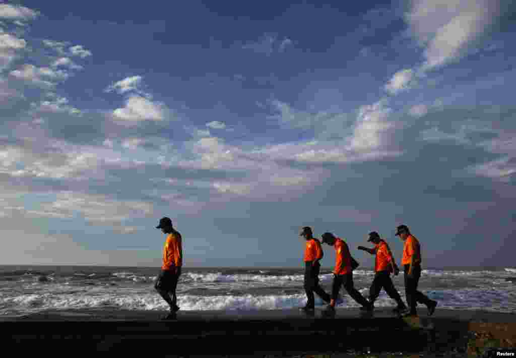 Rescue workers walk along the beach as they search for suspected asylum seekers who were on a boat that capsized, Sukapura beach in West Java, Indonesia, July 25, 2013.