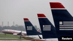 Un vuelo de American despega del aeropuerto Reagan en Washington mientras varios aviones de US Airways se alinean en la terminal.