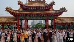 Puluhan pasangan pengantin baru Malaysia berfoto setelah upacara nikah massal yang digelar pada hari kesembilan, bulan kesembilan di kuil Thean Hou di Kuala Lumpur, Malaysia, 9 September 2019. (Foto: AFP)