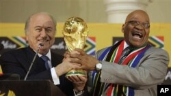 South African President Jacob Zuma, right, laughs as he hands over the trophy to FIFA President Joseph Blatter, left, during the briefing to local and international media on the 2010 Soccer World Cup at the Presidential Guest House in Pretoria, South Afri