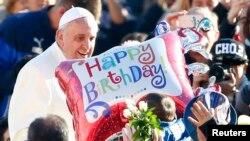 Une fidèle tend un ballon au pape François pour lui présenter des voeux pour le 78ème anniversaire de la naissance du pontif argentin lors d'une audience générale au Vatican, le 17 décembre 2014.