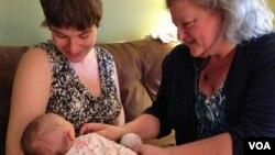 Certified Nurse Midwife Mairi Breen Rothman checks baby Debra as her mother, Beth Drake, looks on. September 25, 2014, VOA, J.Taboh