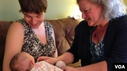 Certified Nurse Midwife Mairi Breen Rothman checks baby Debra as her mother, Beth Drake, looks on. September 25, 2014, VOA, J.Taboh