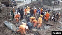 救援人員星期五在雲南省鎮雄縣山體滑坡後搜索受害者
