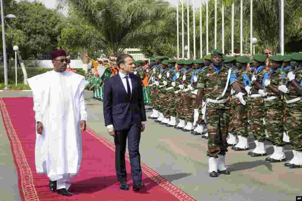 Le président du Niger, Mahamadou Issoufou, et le président français, Emmanuel Macron, inspectent une garde d'honneur au palais présidentiel, à Niamey, au Niger, le 23 décembre 2017.