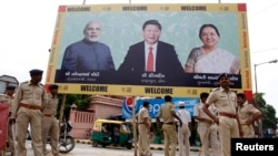 Police stand guard in front of a bill board with images of (L-R) India's Prime Minister Narendra Modi, China's President Xi Jinping and Anandiben Patel, Chief Minister of the western Indian state of Gujarat, ahead of Xi's arrival, in Ahmedabad, Sept. 16, 2014.