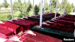 FILE - Coffins containing the bodies of Afghan national army soldiers killed in an April 21 attack on a military base in Mazar-i-Sharif, northern Afghanistan, April 22, 2017.