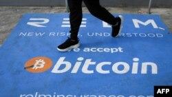 Un homme passe devant une bannière avec le logo du bitcoin pendant la conférence sur les crypto-monnaies Bitcoin 2021 Convention au Mana Convention Center à Miami, en Floride, le 4 juin 2021.